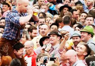 A young man drinks beer on his friend's shoulders at the opening ceremony of the 183rd Oktoberfest beer festival in Munich.