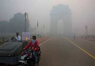 In this Monday, Oct. 31, 2016 photo, a man covers his face with a scarf as he rides in front of the landmark India Gate, enveloped by smoke and smog, on the morning following Diwali festival in New Delhi, India. As Indians wake Monday to smoke-filled skies from a weekend of festival fireworks for the Hindu holiday of Diwali, New Delhi's worst season for air pollution begins, with dire consequences. A new report from UNICEF says about a third of the 2 billion children in the world who are breathing toxic air live in northern India and neighboring countries, risking serious health effects including damage to their lungs, brains and other organs