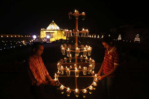 Indians light lamps at Akshardham temple on the eve of Diwali, the festival of lights, in Gandhinagar, India. Diwali is one of Hinduism's most important festivals, dedicated to the worship of the Hindu goddess of wealth Lakshmi.