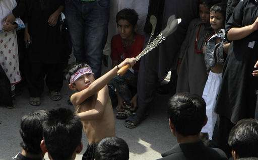 During a procession in Lahore, Pakistan a young boy flagellates himself.