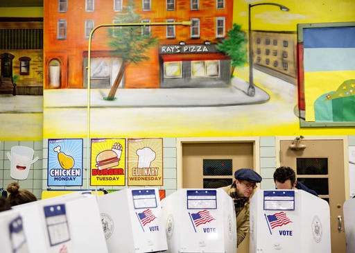 Peter McGough, left, talks with Adam Scheffer as they vote in a school cafeteria in New York. Mc Cough said,