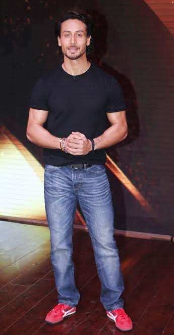 Tiger Shroff was seen in a casual attire. He wore a simple black tee with a trendy pair of red shoes.
