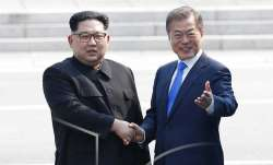 North Korean leader Kim Jong Un, left, shakes hands with