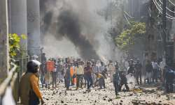 Protestors throw brick-bats during clashes between a group