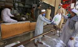 A shopkeeper deals customers with distance to help avoid the spread of coronavirus, in Peshawar, Pak