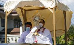 A Catholic priest wearing a protective mask holds a Monstrance with the Sacred Host as he rides a pi