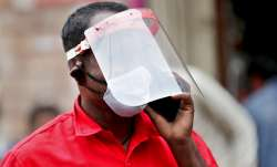 An Indian trader wears a face shield and mask as he talks on his mobile phone at a wholesale fruit m