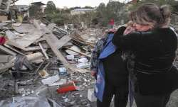 A neighbour comforts home owner, Lida Sarksyan, left, near