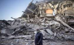 A Palestinian man looks at the destruction of a building