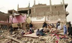 Locals inspect the site of a car bomb attack in Herat