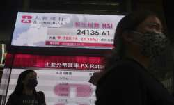 People walk past a bank's electronic board showing the Hong
