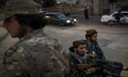 Taliban fighters ride in the back of a pickup truck as