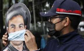 A man adjusts a face mask on a promotional cardboard cutout