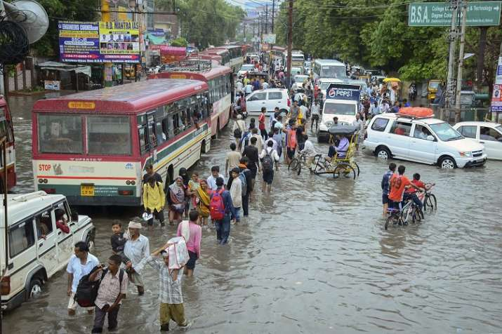 Pedestrians wade across a waterlogged road after monsoon