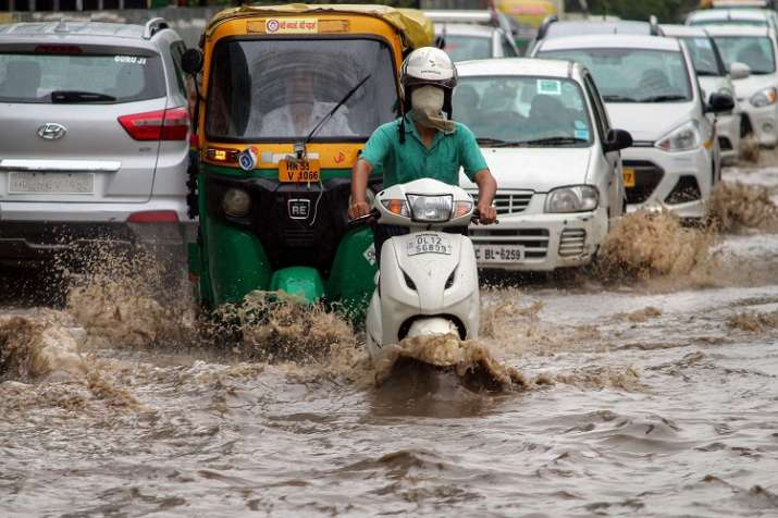Commuters wade through water-logged road in Gurgaon as