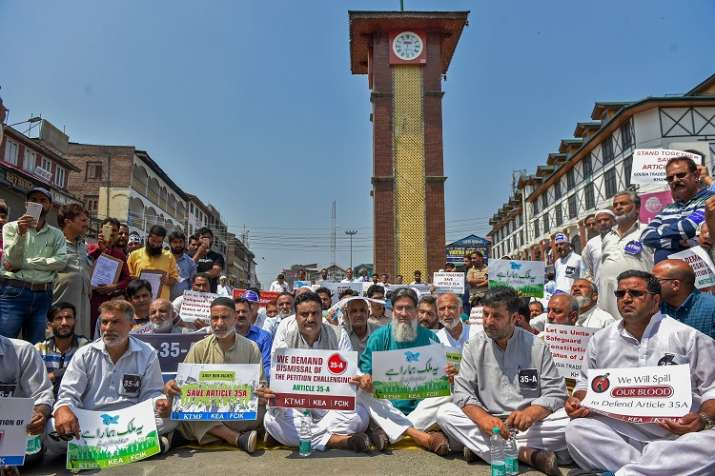 Kashmiri traders hold placards and raise slogans