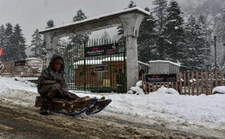 A child enjoy sledging on a road in Srinagar